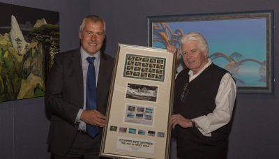 Isle of Man Post Office Chairman presents Roger Dean with a framed set of stamps on opening night of his exhibition at the Manx Museum in Douglas